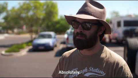 A man with a beard, wide brimmed hat and sunglasses on stands in front of the camera in a carpark as he's being interviewed. The subtitles read Absolutely.