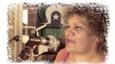 An indigenous woman sings into a microphone. She has soft curly brown hair. A Torres Strait flag hangs from the wall behind her.