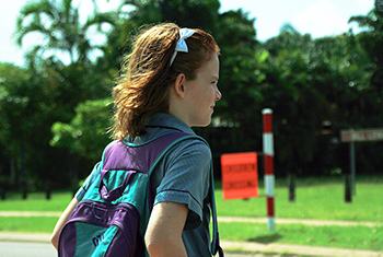 The blurred background shows a striped pedestrian crossing post and flag. Close up is the image of a school girl. She has a headband with a bow in her hair. She's in school uniform and is carrying her school backpack. The girl is standing at the edge of the path, ready to cross safely.