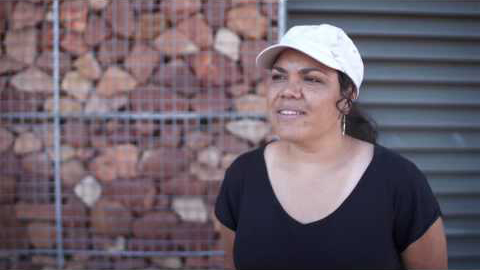 An indigenous woman stands in front of a building, She's wearing a black t-shirt and white hat. Her hands are behind her back as she is being interviewed.