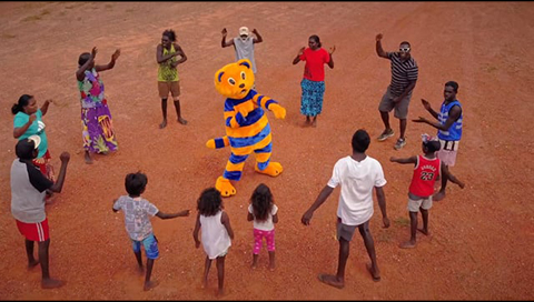 Thirteen Aboriginal peoples are standing in a circle dancing. Hector the road safety cat is standing in the middle of the circle and is also dancing.