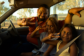 Three indigenous people are sitting in the front of a ute. On the drivers side is a man with his left arm resting on the back of the passenger seats. Two young girls sit in the other two seats. All people are wearing their seatbelts and with their right hand, they make a 'V' shape using their pointer and middle fingers.
