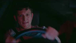 A man is behind the wheel of a speeding car at night.