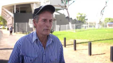 A man stands in front of a stadium as he's being interviewed. He's wearing a blue and white striped collared shirt and a navy blue hat. His mouth is slightly open as he is about to answer a question.