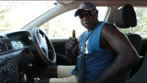 An indigenous man sits in the drivers seat of his car. His seatbelt is buckled in and he is giving a thumbs up.