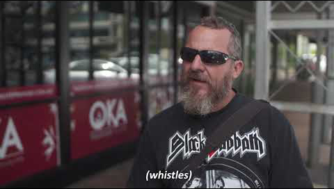 A man with a beard wearing sunglasses stands in front of the camera as he's being interviewed on a sidewalk. The subtitles read