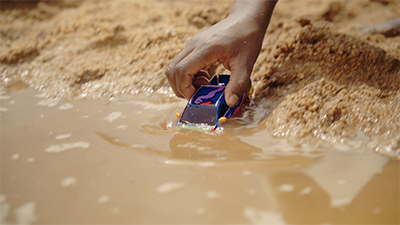 Image of hand pushing toy car into water